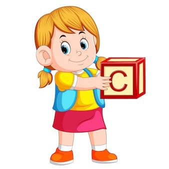 Маленькая девочка, держащая кубик алфавита