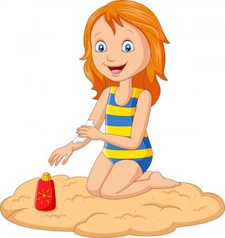 Маленькая девочка в купальнике наносит солнцезащитный крем на руку