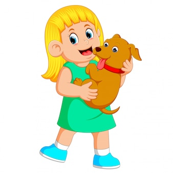 A little girl is holding her brown puppy with her hands