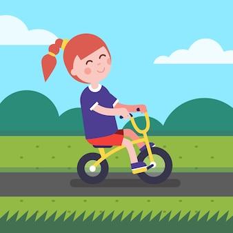 Bambina in sella a bicicletta in bicicletta su una pista ciclabile