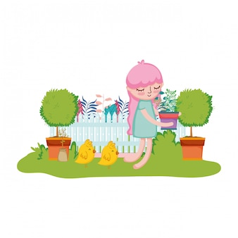 Little girl lifting houseplant with fence and chick