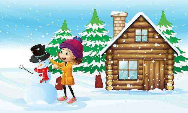 Little girl making snowman in the field