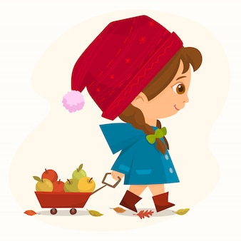 Little girl pulling a wheelbarrow with apples