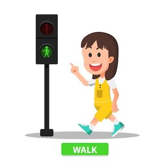 Маленькая девочка начинает идти, когда индикатор пешеходного перехода загорается зеленым