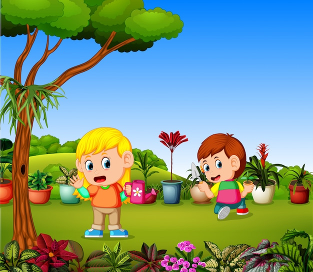 Little girl watering plants and a boy planting in a garden