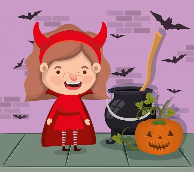Little girl with devil costume and cauldron and pumpkin