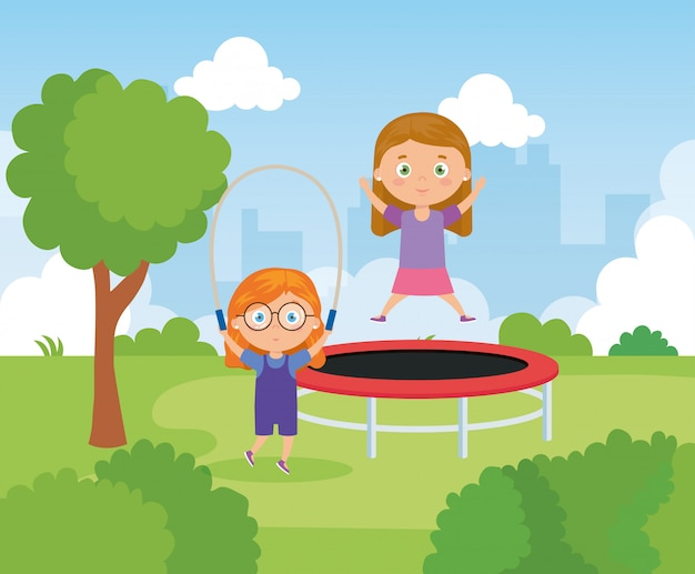 Little girls with trampoline jump and rope jump in park landscape