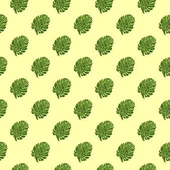 小さな緑の斜めのモンステラはシームレスなパターンを残します。明るい黄色の背景。ネイチャープリント。