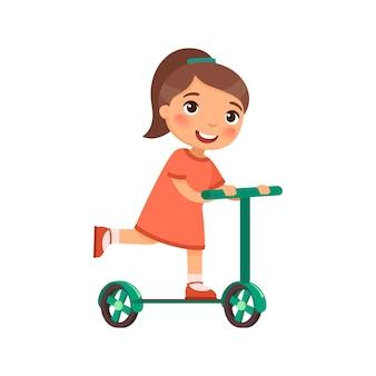 小さな幸せな女の子はスクーターに乗る
