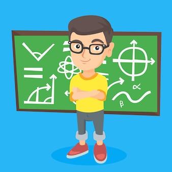 Little schoolboy standing in front of blackboard.