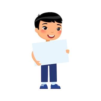空のバナーを保持している小さな笑顔の少年。白紙のシートでかわいい小学生。プラカードで幸せな若いアジアの子供