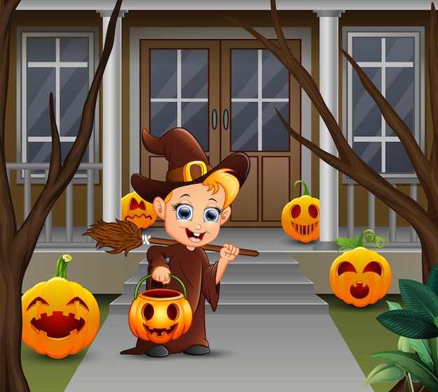 Little witch holding pumpkin basket standing in front of the house
