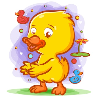 Little yellow duck dancing on the green grass with the happy face