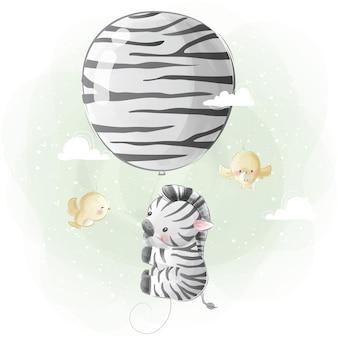 風船で飛んでいる小さなシマウマ