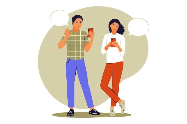 Живое общение двух друзей. парень и девушка стоя с телефонами и пузырями речи. векторная иллюстрация. плоский.