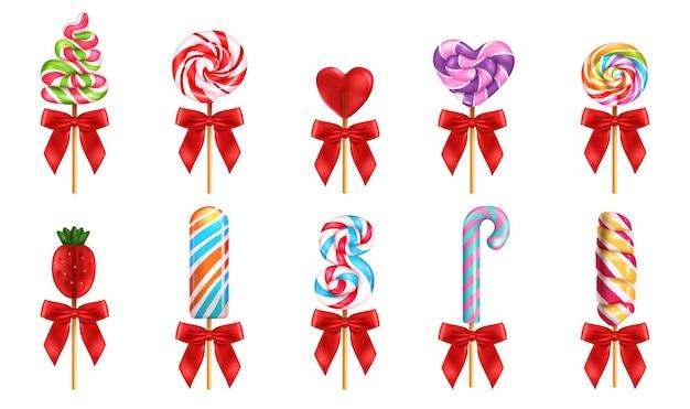 分離された甘いキャンディーのさまざまな形や色の赤い弓の現実的なセットとロリポップ