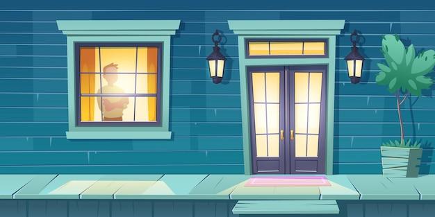 Одинокий мужчина со скрещенными руками стоит у окна на ночной улице.