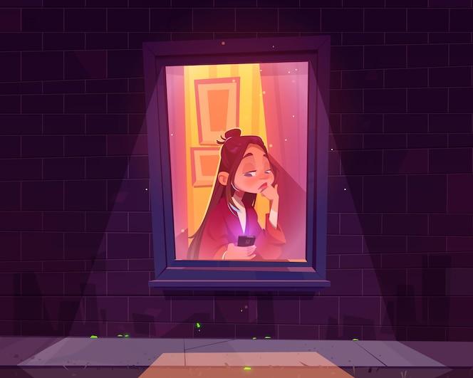 孤独悲伤的女孩独自坐在窗前,手里拿着智能手机