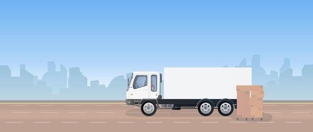 トラックとボックス付きパレット。トラックが道路に立っています。カートンボックス。貨物の配達と積み込みの概念。 。