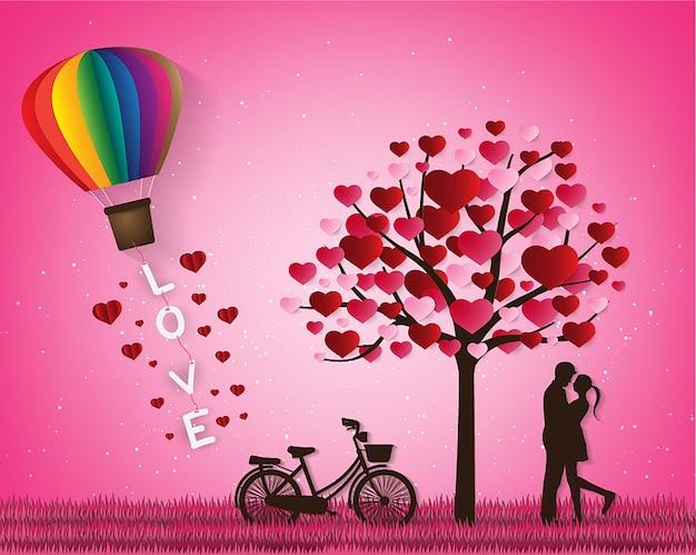 사랑과 발렌타인 데이 연인들은 초원에 서 있고 종이 예술 하트 풍선은 떠 있다