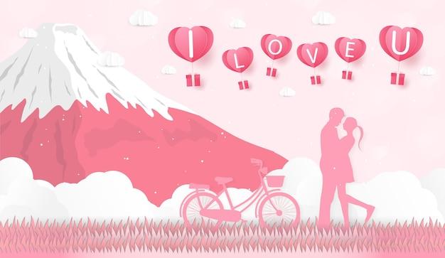 사랑과 발렌타인 데이 연인들은 초원에 서서 종이 예술 하트 모양 풍선이 떠 있다