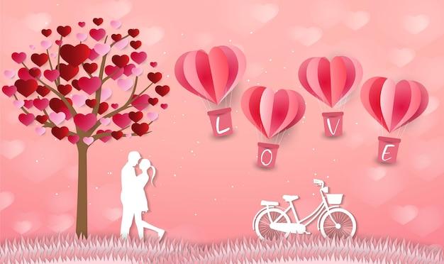 Любовь и день святого валентина влюбленные стоят на лугах у воздушного шара в форме сердца из бумаги.