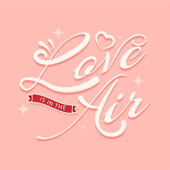 Love is in the air font with heart on pastel red background.