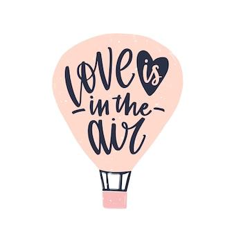 Рукописная фраза love is in the air элегантным курсивным каллиграфическим шрифтом на воздушном шаре