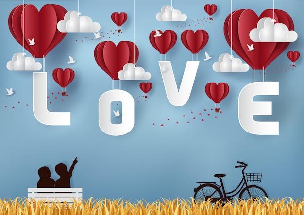 バレンタインデーのコンセプト男の子と女の子がバイクでテーブルの上に座っています。文字loveと空に浮かぶ風船