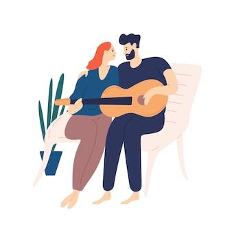 ベンチに座ってギターを弾く素敵なカップル。ロマンチックなデートで抱きしめたり歌を歌ったりする若い愛らしい男性と女性のペア。愛の少年と少女