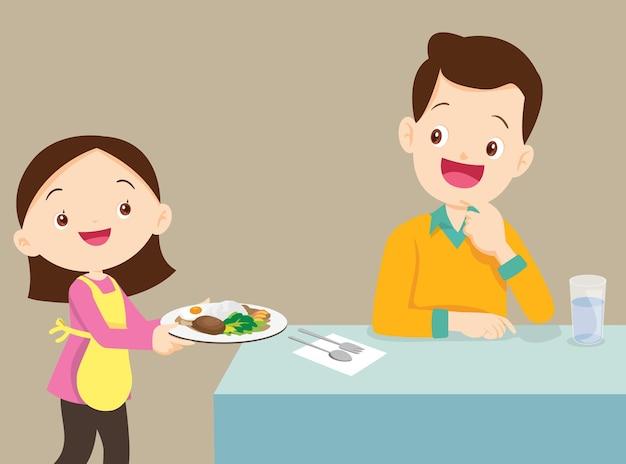 아버지에게 음식을 제공하는 사랑스러운 딸, 가족은 요리를 즐깁니다.