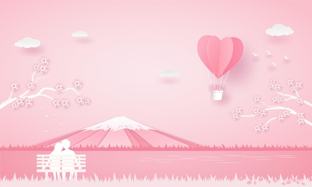 Lover sit on the chair and looking to balloon heart below the sakura tree and see the fuji mountain in pick color.