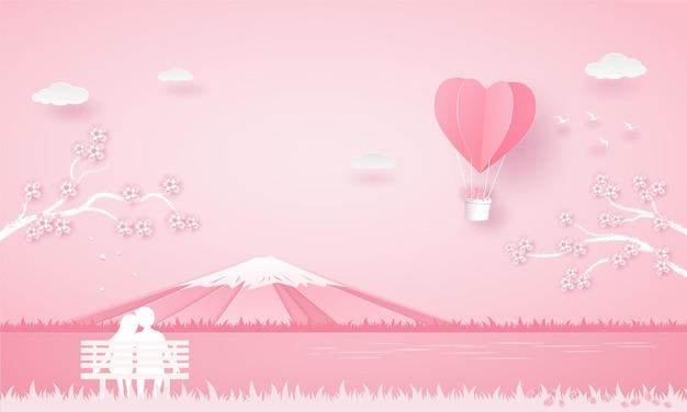 恋人は椅子に座って、桜の木の下の風船のハートを見て、富士山をピックカラーで見ます。