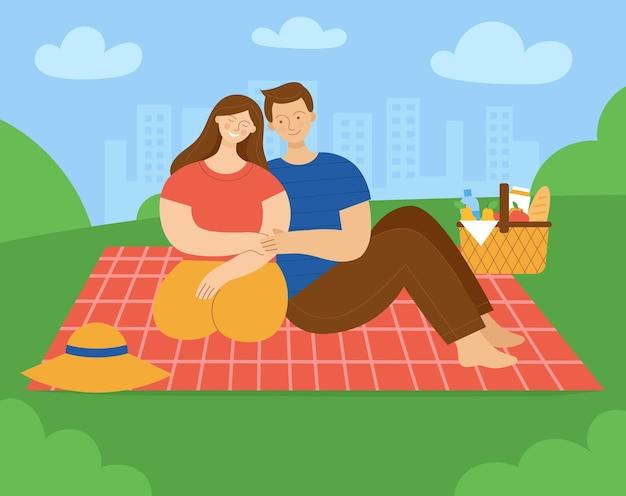 Влюбленная пара на пикнике в парке и женщина сидит на пледе и улыбается
