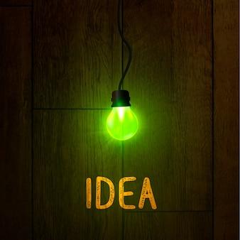 ダークウッドの質感の明るいランプ。抽象的なアイデアのシンボル。ランプは緑色のきらめく光で輝いています。