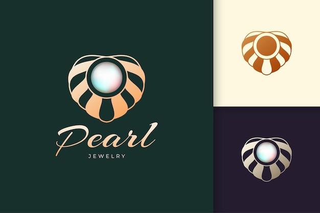 조개 로고가 있는 고급스럽고 우아한 진주는 미용 및 패션 브랜드에 적합한 보석 또는 보석을 나타냅니다.
