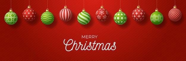 豪華なメリークリスマス水平バナー。華やかな赤と緑の現実的なボール付きのクリスマスカードは、赤のグラデーションのモダンな背景のスレッドにハングアップします。図。あなたのテキストのための場所
