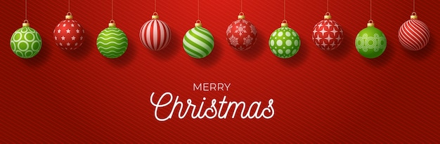 Luxury merry christmas horizontal banner. christmas card with ornate red and green realistic balls hang on a thread on red gradient modern background.  illustration. place for your text