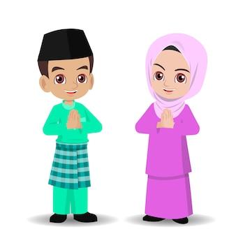 Malay boy and girl in traditional clothes greeting selamat hari raya