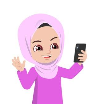 携帯電話を持っているマレーのかわいい女の子が手を振った