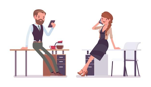Мужской и женский офис возле стола, работающего с телефоном