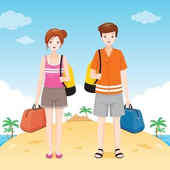 Мужчина и женщина путешественник с водонепроницаемой сумкой, стоя на пляже вместе