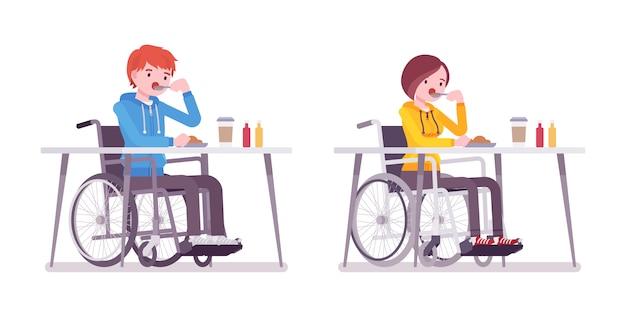 Мужчина и женщина молодые пользователи инвалидной коляски едят за столом