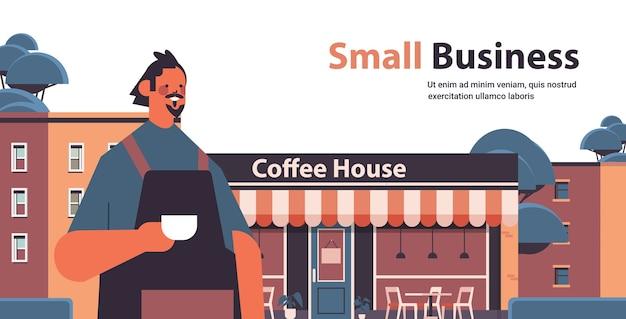 Мужчина бариста в униформе владелец кафе в фартуке, стоя возле кофейни горизонтальный портрет копией пространства векторная иллюстрация