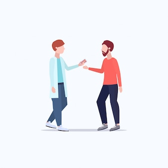Male doctor giving antibiotics to male patient pharmacist offering pills medication healthcare medical consultation concept full length