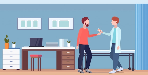 Male doctor giving antibiotics to male patient pharmacist offering pills medication healthcare medical consultation concept modern hospital office interior full length  horizontal