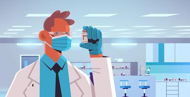 Мужчина-врач в маске держит флакон с вакциной covid-19 для инъекций вакцинация иммунизация против коронавирусной болезни медицинская концепция интерьер лаборатории горизонтальная иллюстрация