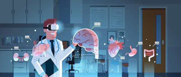 Male doctor wearing digital glasses looking at virtual reality organs