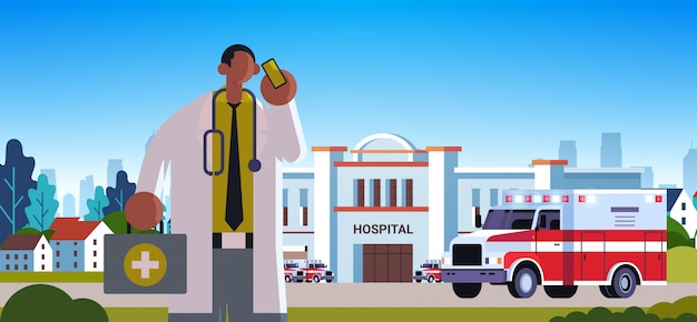 Male doctor in white coat with first aid kit talking on mobile phone medicine healthcare concept medical clinic worker with stethoscope modern hospital building exterior portrait horizontal