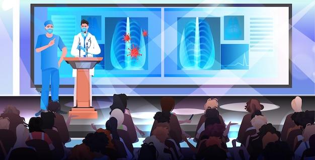 코로나 바이러스 의료 회의 개념에 대한 마이크 싸움과 트리뷴에서 연설을하는 마스크의 남성 의사
